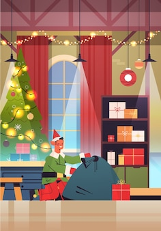 Green elf boy santa claus helper with sack full of gifts happy new year merry christmas holidays celebration concept workshop interior full length vertical vector illustration