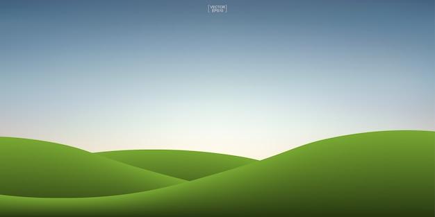 緑の草の丘と夕焼け空の背景