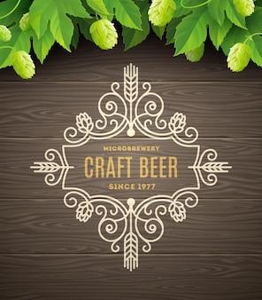 緑のホップと木の板の背景にビールのエンブレムが繁栄します