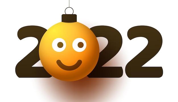 Поздравительная открытка на новый год 2022 года с улыбающимся смайликом, который висит на нитке, как рождественская игрушка, мяч или безделушка. новый год эмоции концепции векторные иллюстрации