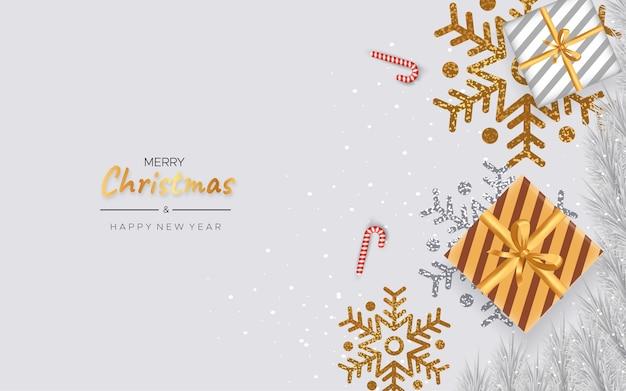 グリーティングカード、明けましておめでとうございます。メタリックゴールドのクリスマススノーフレークと白い背景の上のギフトボックス