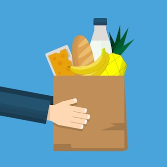 Grocery store and food delivery with hands holding a paper shopping bag full of goods and product including bread, milk, banana, pineapple and cheese.