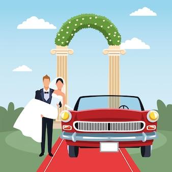 Жених держит невесту на руках и красный классический автомобиль в новобрачных