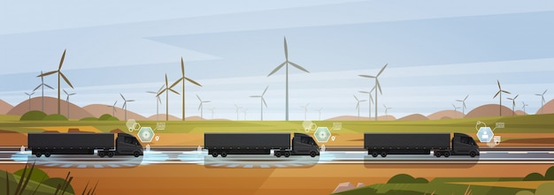 Group of black cargo truck with trailers driving on countryside road over nature landscape horizontal
