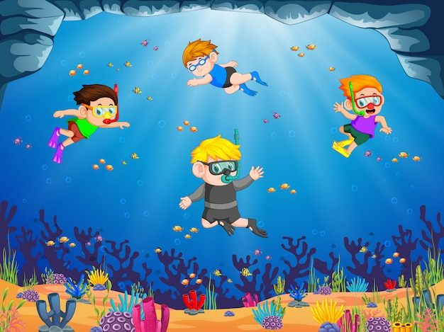 A group of children are diving under the blue sea with their friend