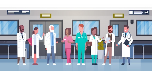 Group of doctors in hospital corridor diverse medical workes in modern clinic