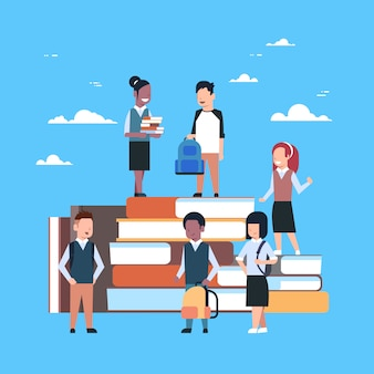 Group of little children on stack of books school education concept