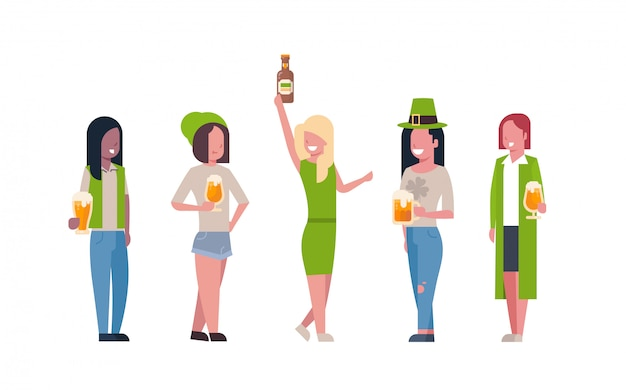 Group of mix race women in green clothes drink beer celebrating happy st. patricks day isolated