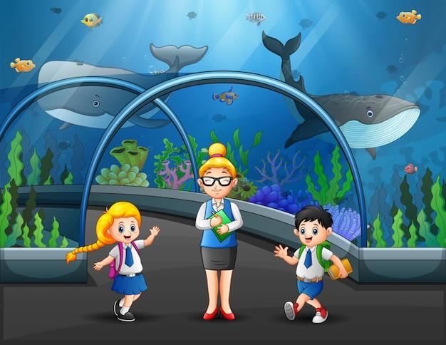 Группа детей, наблюдая рыб на экскурсии в аквариуме