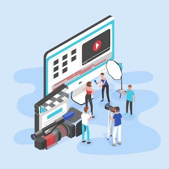 巨大なコンピューターディスプレイ、カチンコ、カメラのそばに立ってビデオインタビューを撮影している人々のグループ
