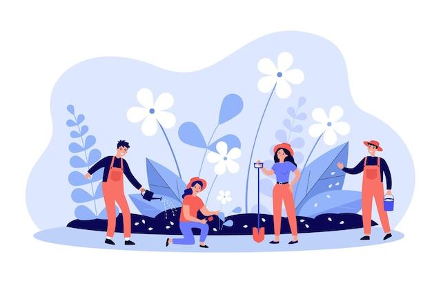 Группа людей с инструментами, работающими в саду. садовники сажают и поливают цветы весной