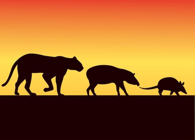일몰 풍경 그림에서 야생 동물 실루엣의 그룹