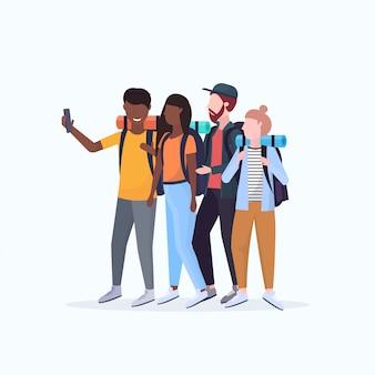 Группа туристов туристы с рюкзаками, принимая селфи фото на смартфон камеры пешие прогулки концепция смешать расы путешественников на поход полная длина белый фон плоский