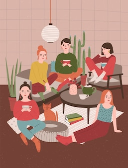 Group of young women sitting in room furnished in scandinavian style, drinking tea and talking to each other