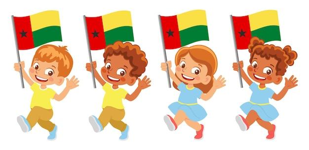 Флаг гвинеи-бисау в руке. дети держат флаг. государственный флаг гвинеи-бисау