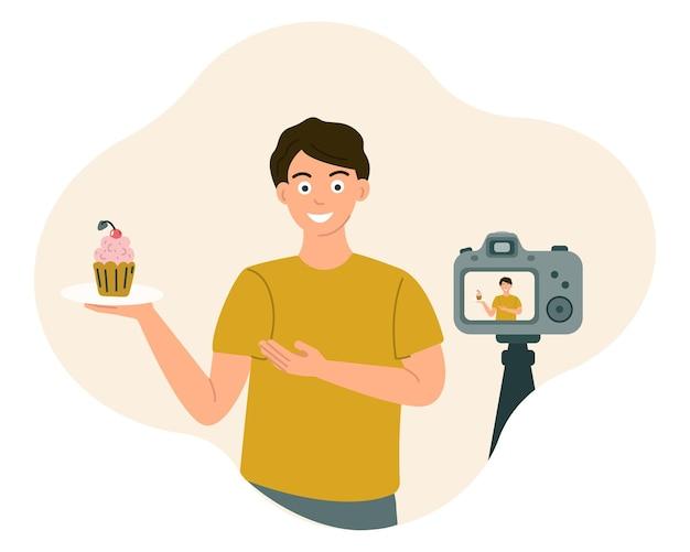음식에 대한 남자 블로거는 비디오를 녹화하면서 카메라 앞에서 미소를 지으며 음식을 보여줍니다.