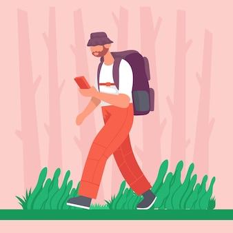 男はバックパックを持って、携帯電話を手に持ってハイキングをします。屋外でのハイキングのコンセプト