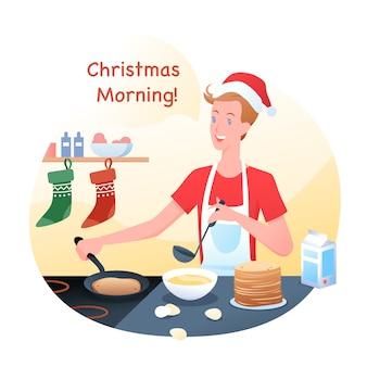 男は家でクリスマスの帽子、冬の休日でパンケーキを調理しています。クリスマスの朝のルーチン。