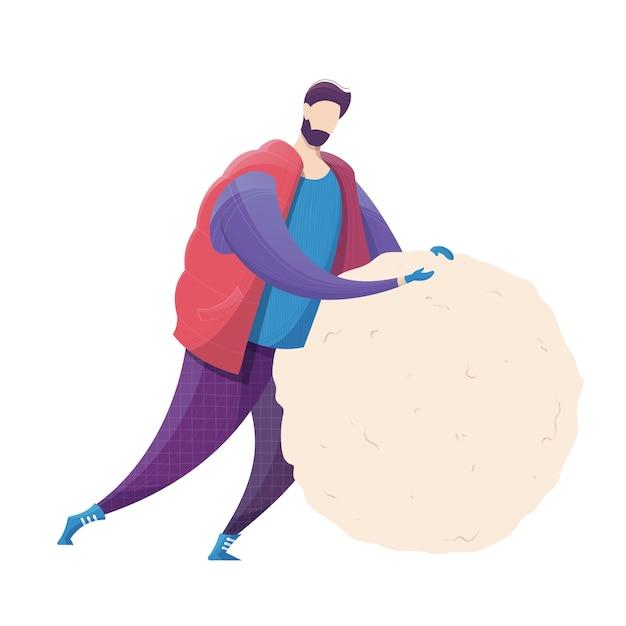 男は雪だるまの冬の野外活動のために大きな雪玉を作ります
