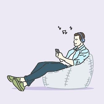 블루투스 헤드폰을 사용하여 전화를 들고 아늑한 안락 의자에 앉아있는 사람은 노래를 들어