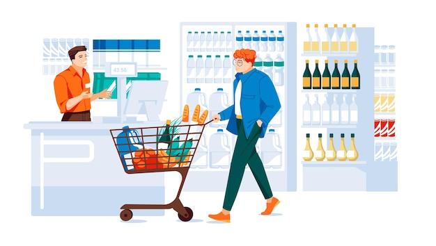Парень с тележкой, полной товаров в супермаркете возле кассы интерьер супермаркета
