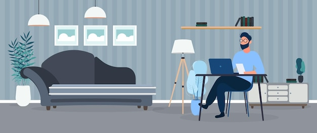 A guy with glasses sits at a table in his office. a man works on a laptop. office, sofa, bookshelf, business man, floor lamp. office work concept. .