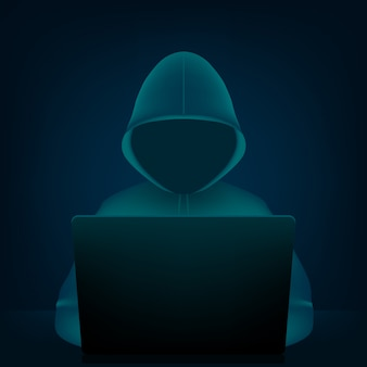 Hacker with hoodie, dark obscured face and pc laptop.