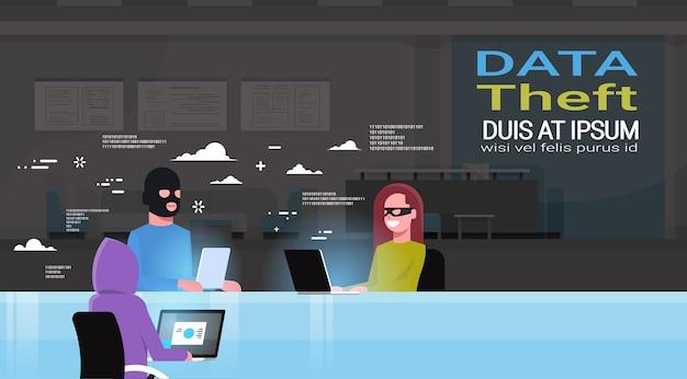 Hackers group wearing black masks sitting at gadgets