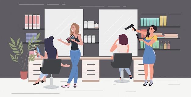 Hairdresser using hair dryer making hair style to her client women testing eyeshadow palette beauty salon interior horizontal full length