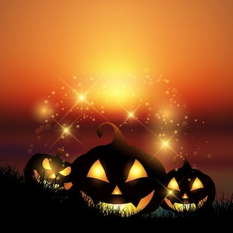 Halloween background with pumpkins against a sunset sky