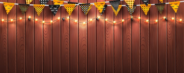 Halloween background with string light and halloween buntings on wood background