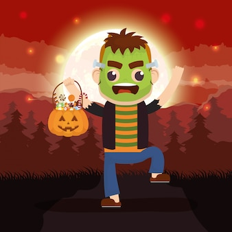 Halloween dark scene with pumpkin and kid disguised frankenstein