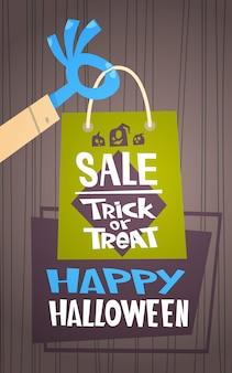 Halloween sale seasonal discount concept monster hand holding shopping bag