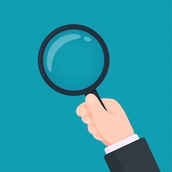 The hand of a business man with a magnifying glass inspection concept.