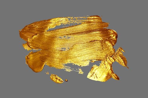 Рука рисунок золотой мазок краски пятно на сером фоне, ручная работа