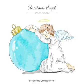 Рука обращается ангел фон, опираясь на рождественский бал
