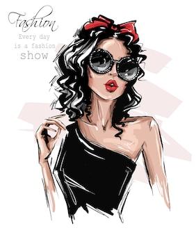 手描きのサングラスで美しい若い女性。彼女の頭に弓を持つスタイリッシュな女の子。ファッション女性を見てください。