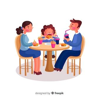 Famiglia disegnata a mano che si siede intorno all'illustrazione della tavola