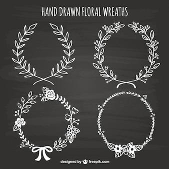 Hand drawn floral wreaths on blackboard