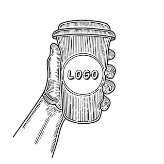 Hand drawn hands holding cup of coffee. place for your logo. sketch.