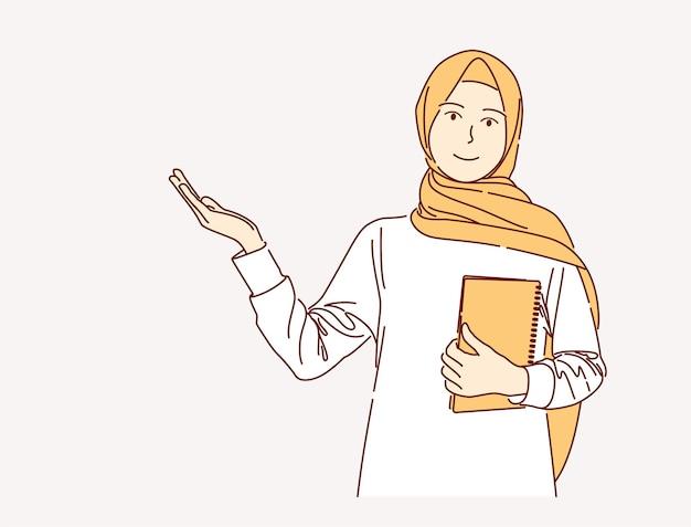 고립 된 분홍색 배경 위에 책을 들고 이슬람 여자의 손으로 그린 그림