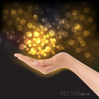 Hand and gold bokeh light on black luxury background.