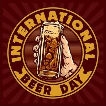 世界ビールの日を祝うためにビールのバッジのガラスを手に持ってください