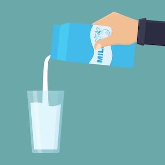 손으로 우유 상자를 잡고 유리 평면 그림에 우유를 부어