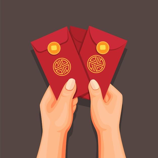 封筒にangpaoのお金を持っている手、中国の旧正月を祝う