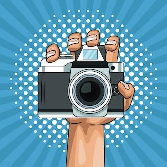 Hand holding camera pop art cartoon