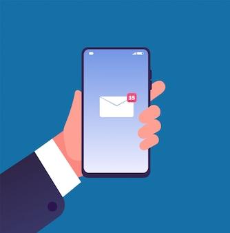画面上の新しいメールメッセージと携帯電話を持っている手