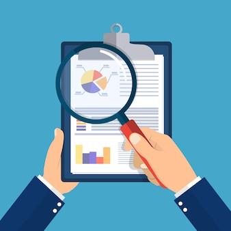 재무 보고서와 돋보기 클립 보드를 들고 손.