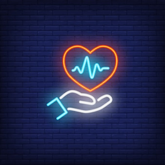 Mano che tiene il cuore con segno al neon cardiogramma