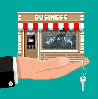 Hand holding shop or commercial property with key. real estate business promotional, startup. selling or buying new business. small european style shop exterior. flat vector illustration